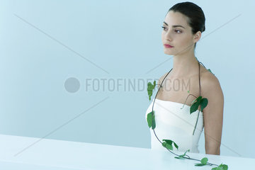 Young woman with leafy vine hanging around shoulders