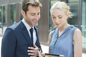 Real estate agent using digital tablet to show property to potential buyer