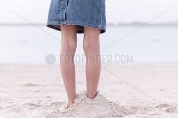 Girl standing on beach with feet buried in sand  low section