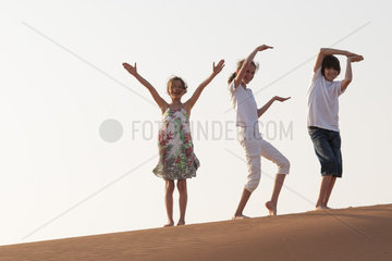 Children walking in desert  making gestures with arms