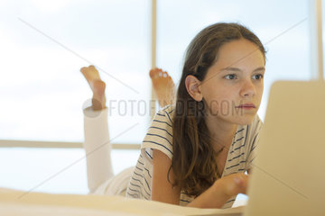 Preteen girl lying on stomach using laptop computer