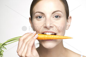 Young woman biting into carrot  portrait