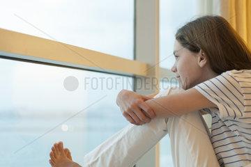 Preteen girl hugging knees  looking out window