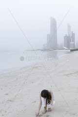 Girl looking for seashells at the beach