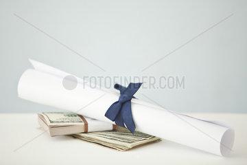 College diploma set atop stacks of cash