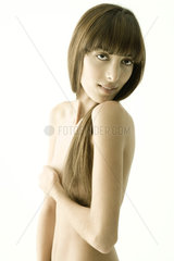Nude young woman covering chest  looking over shoulder at camera