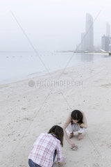 Girls looking for seashells at the beach