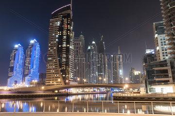 Skyscrapers illuminating marina by night