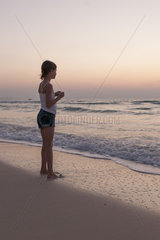 Girl standing on beach looking at sea