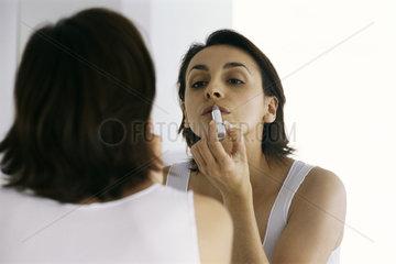 Woman looking in mirror  applying lipstick
