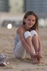 Preteen girl sitting on beach with barefeet  hugging knees