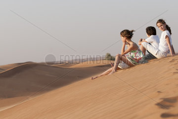 Children sitting together on sand dune looking at view