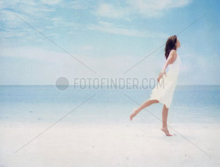 Woman at beach  balancing on one leg