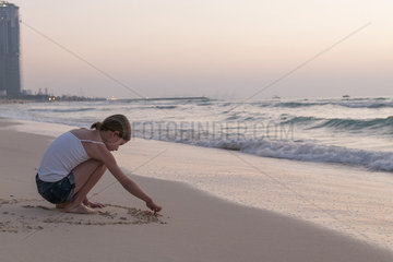 Girl drawing in sand on beach
