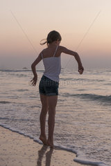 Girl playing on beach  rear view