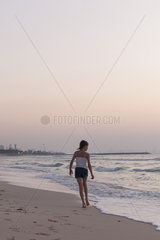 Girl walking on beach  looking at sea