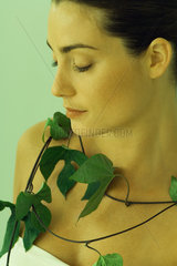 Young woman with leafy vine around neck  close-up