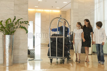 Bellhop assising mother and children with luggage in hotel lobby