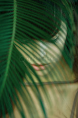 Woman standing behind leaves  eyes closed  selective focus
