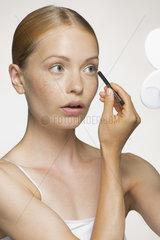 Young woman applying eyeliner