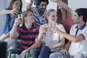 Friends watching sports match on television together celebrate