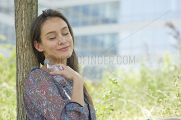 Woman relaxing outdoors with water bottle  eyes closed