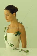 Young woman with leafy vine hanging around shoulders  eyes closed
