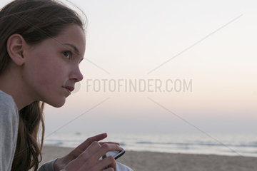 Girl using smartphone on beach  side view