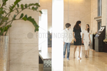 Mother and children walking in hotel lobby