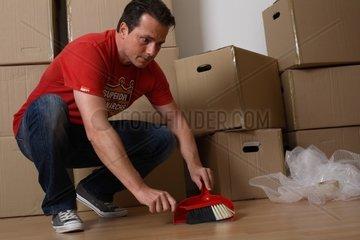 Mann vor Umzugskartons fegt zusammen