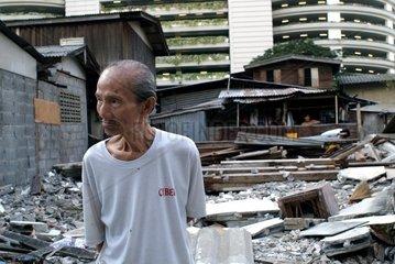 Ein alter Thailaender steht vor einem Abbruchgebiet