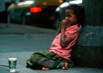 08.02.2004  Bangkok  Bangkok  THA  THAILAND  Thailaendisches Bettlermaedchen sitzt an einem Betonpfeiler und sammelt Geld