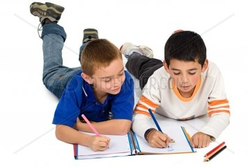 kids drawing on a notebook on the floor isolated over a white background