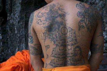 Junger Moench in Vang Vieng hat viele Tattoos auf dem Ruecken