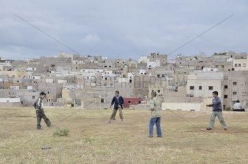 Jungs spielen Fussball  dahinter Haeuser und Wohnungen der aermeren Bevoelkerung  Siedlung ausserhalb von Fes  Marokko  Afrika