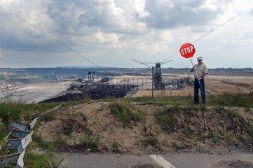 Mann mit Stopschild steht am Rande eines Tagebaues