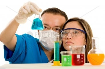 Couple of young chemistry students over a white background