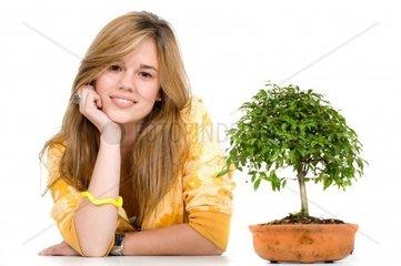 pretty girl portrait with a boinsai tree next to herisolated