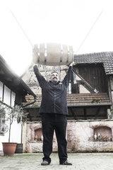 Edelbrenner Markus Wurth stemmt ein Whiskyfass in die Hoehe