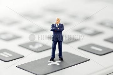 Businessman figurine standing on calculator