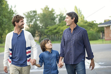 Fathers holding hands with son outdoors