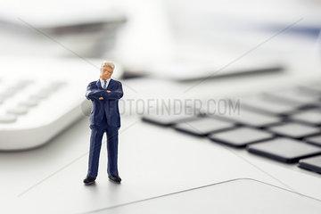 Businessman figurine standing on laptop computer keyboard