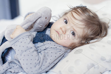 Baby girl lying down with stuffed toy  portrait