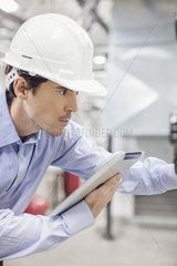 Engineer referencing digital tablet while working inside industrial plant