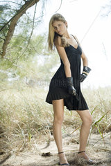 Teenage girl modeling dress and gloves outdoors