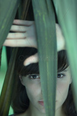 Woman standing behind palm leaves  looking at camera