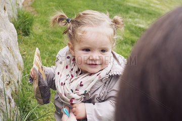 Baby girl outdoors  bag of snacks in hand