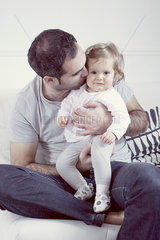 Father holding baby girl on lap  kissing her cheek
