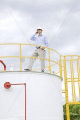 Engineer inspecting industrial storage tank