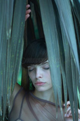 Woman standing among palm leaves  eyes closed